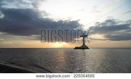 Sunken Cemetery cross in Camiguin Island, Philippines. Large crucafix marking the underwater sunken cemetary of the coast of camiguin island near mindanao in the Philippines. Catholic cross in the water on the background of sky and clouds.. The Sunken Cem