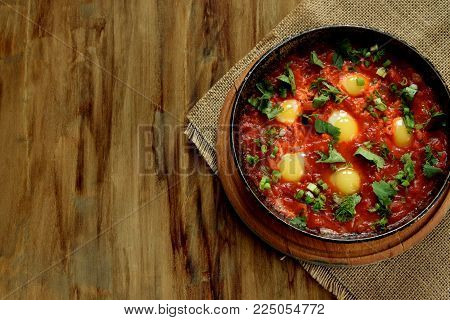 Fried eggs with tomato sauce and parsley in a cast iron pan on wooden background. Shakshuka a traditional meal of the Jewish cuisine