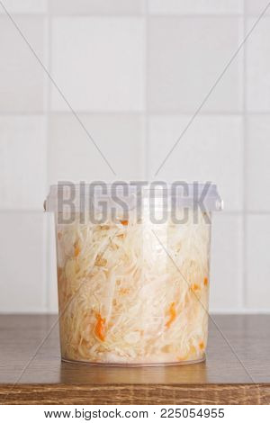 Marinated cabbage in plastic bucket standing on the kitchen table