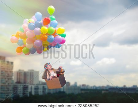 Happy girl flying in a cardboard box on the balloons. Flying high above the city. The concept of children's dreams, journey, freedom