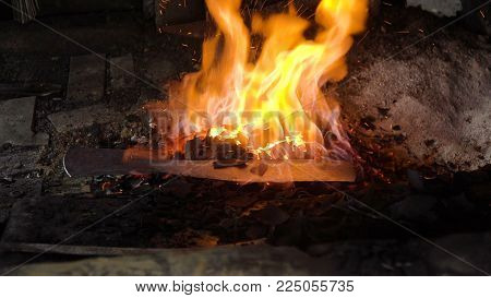 Blacksmith furnace with a hot iron, burning embers, sparks. Blazing furnace with burning coal at the blacksmith's. Blacksmiths make machete. Philippines.