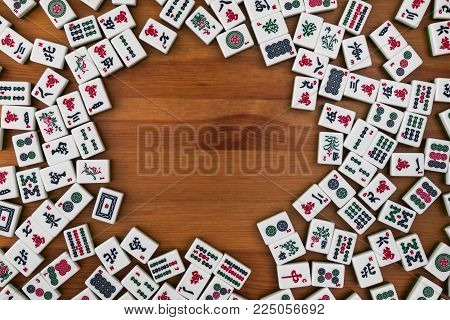 White-green tiles for mahjong on a brown wooden background. Empty place in the center.