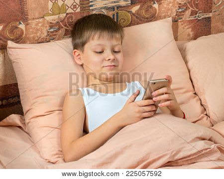 Boy With Phone In Bed