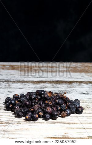 Dry Juniper Berries On An Old White Wooden Table, Non Uniform Background With Free Space For Text