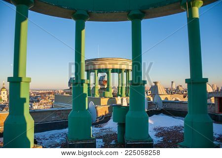 Rotunda, columns of green color on the roof, against the blue sky.