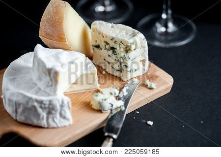 Assortment of cheeses  on a wooden plate with vintage silver knife and two wine glasses. Vertical. Macro image. Black background. Horisontal