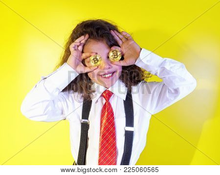 Little boy close his eyes with bitcoin coins on a yellow background