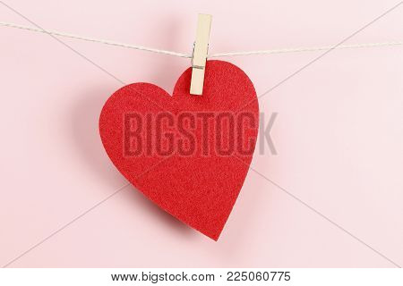 red felt heart caught on clothesline with peg against pink background