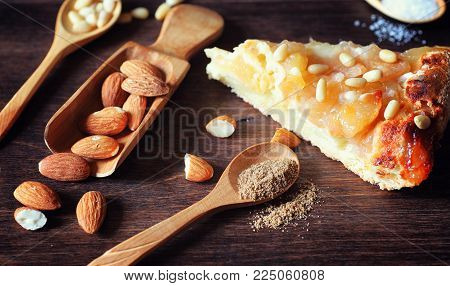 Charlotte with apples and nuts. Preparation of apple baking with nuts and honey. Dessert baked goods from apples and nuts with honey on a wooden table.