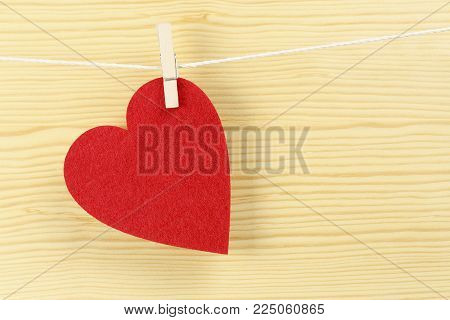 red love heart on clothesline against wood