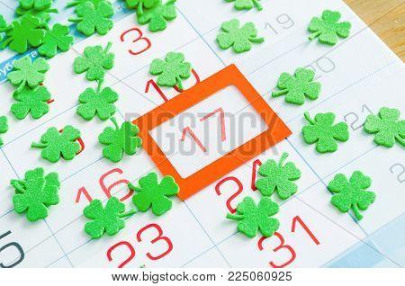St Patrick's Day festive background. Green quatrefoils covering the calendar with orange framed 17 March - St Patrick's day holiday date. Festive St Patrick's day postcard