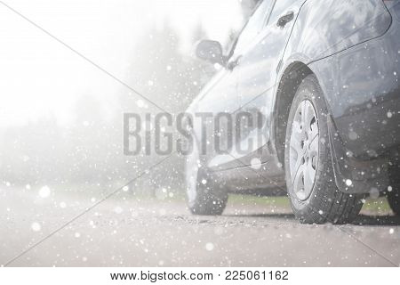A car on rural road in the first autumn snow. The first winter snow on the country road, the car under the snow.