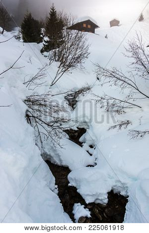 Snow and little creek in the mountains
