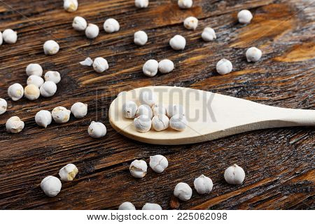 raw chickpeas in a spoon and scattered on a wooden background, organic food, vegetarian cuisine
