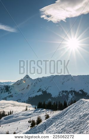 Snow and sun on the top of the mountains and fog down the valley