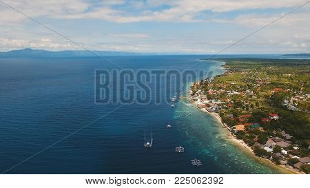 Aerial view of beautifulisland with white sand beach, Moalboal, boats, hotels and tourists. Tropical lagoon with turquoise water and white sand. Seascape: Ocean and beautiful beach paradise. Philippines, Cebu.Travel concept.