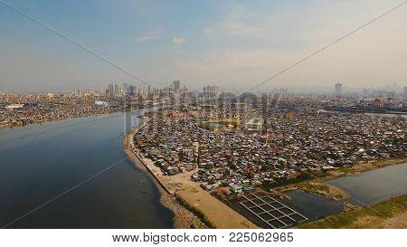 Aerial view poor district of Manila slums, ghettos, wooden old houses, shacks. Slum area of Manila, Philippines. Manila suburb, view from the plane.