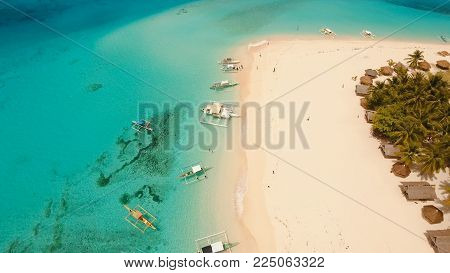 Aerial view of beautiful tropical island Daco with white sand beach. View of a nice tropical beach from the air. Beautiful sky, sea, resort. Seascape: Ocean and beautiful beach paradise. Philippines. Travel concept.