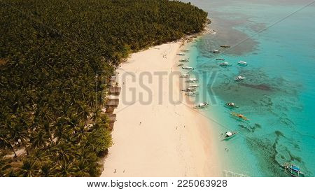 Aerial view of beautiful tropical island Daco with white sand beach. View of a nice tropical beach from the air. Sea, resort. Seascape: Ocean and beautiful beach paradise. Philippines. Travel concept.