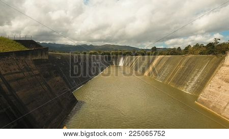 Aerial view Dam on the lake in the rainforest on the island. Water flowing from the dam, Water for Irrigation countryside. Water Cascades Over Lake Bohol island, Philippines..