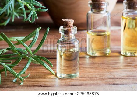 A bottle of rosemary essential oil with fresh rosemary twigs and bottles in the background