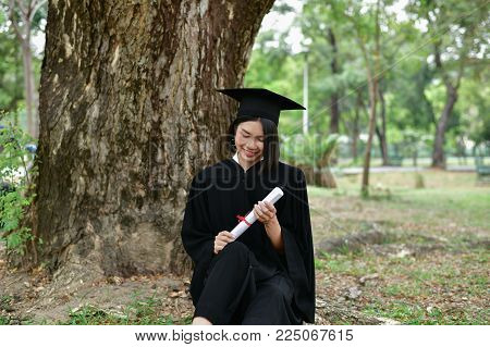 Graduation Concept. Graduated students on graduation day. Asian students are smiling happily on the graduation day. Students wear graduation gowns in the garden