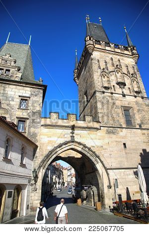 PRAGUE, CZECH REPUBLIC - AUGUST 23, 2016: People walking and look around Lesser Bridge Tower from the Charles Bridge (Karluv Most) in Prague, Czech Republic
