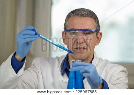 Microbiology Analyst Working With Pipette In Laboratory. Researcher Wearing Blue Protective Gloves,