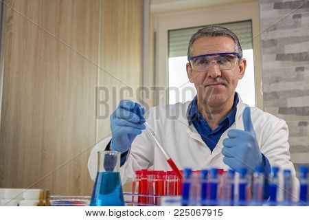 Smiling Lab Technician Giving Thumbs Up In Laboratory. Laboratory Researcher Filling Test Tubes With