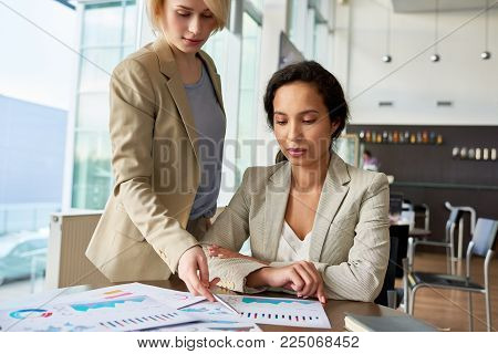 Confident young white collar workers in formalwear analyzing results of accomplished work while gathered together at spacious open plan office
