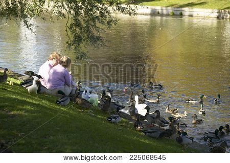 CAMBRIDGE, UK: COUPLE FEEDING DUCKS ON THE BANK OF THE RIVER CAM, 19TH SEPTEMBER 2004, CAMBRIDGE, UK