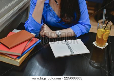 Education Concepts. Asian women are working in a restaurant. Asian women are reading a book in a restaurant.  Asian women relaxing in a restaurant.  Women spend time reading books in the restaurant.