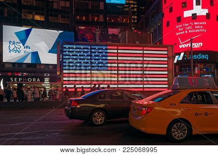 New York, USA - june 06, 2015: Time Square at night. Signage lights illuminate the road. A flag of the USA shines with its colors. Taxis, cars and people passing. Time Square, New York.