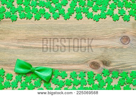 St Patricks Day Background, Double Border With Green Quatrefoils And Bow Tie On The Wooden Backgroun
