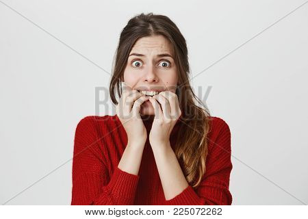 Portrait of wishful young woman in casual clothes with dark hair in ponytail, biting nails of fingers, being troubled, feeling nervous before important event. Body language