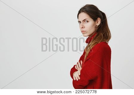 Profile of beautiful girl with ponytail in warm red sweater posing at studio, keeping arms folded, having offended look, frowning face, showing her dislike, negative attitude and reaction.