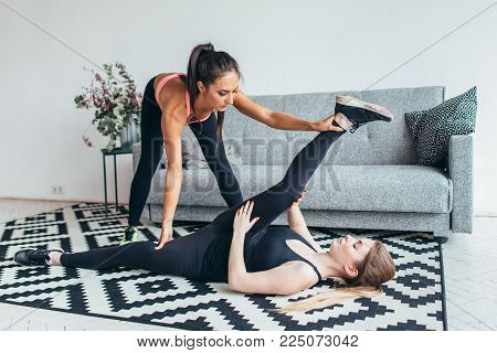 Fit young woman doing stretching exercises with the help of personal trainer at home.