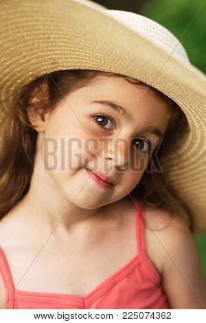 Portrait of smiling beautiful toddler in wide-brimmed hat at green of summer park.