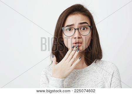 Close-up portrait of young interesting female student in glasses with upset expression and lifted eyebrow, holding fingers on chin, over white background. Girl sees injured stray dog and worries.
