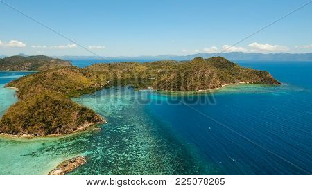 Aerial view: Lagoon with blue, azure water in the middle of small islands and rocks, Palawan. Beach, tropical island, sea bay and lagoon, mountains with forest, Coron. Busuanga. Seascape, tropical landscape. Philippines. Travel concept