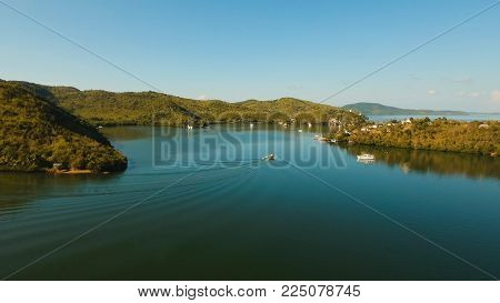 Seascape with a tropical bay surrounded by mountains on the island. Aerial view: Beautiful tropical sea bay. Scenic landscape with mountain islands and blue lagoon. Coron, Philippines, Palawan, Busuanga. Travel concept.