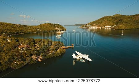 Aerial view: White Seaplane parked in the sea bay of the tropical island. Hydroplane in the lagoon and coastline. Philippines, Palawan, Busuanga. Travel concept