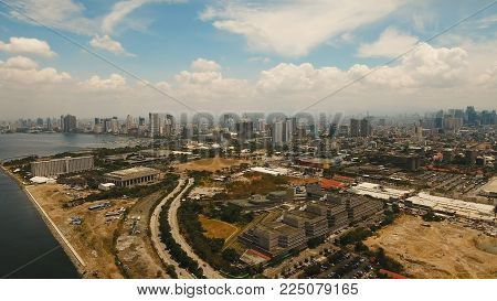 Aerial view of Manila city. Fly over city with skyscrapers and buildings. Aerial skyline of Manila . Modern city by sea, highway, cars, skyscrapers, shopping malls. Makati district. Travel concept.
