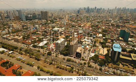 Aerial view of Manila city. Fly over city with skyscrapers and buildings. Aerial skyline of Manila. Modern city by sea, highway, cars, skyscrapers, shopping malls. Makati district. Travel concept.