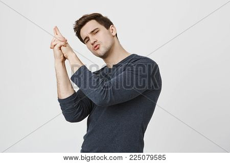 Confident young dark-haired male student in casual clothes makes shooting gesture, ready to reach great success. Good looking man makes gun gesture with hands and looks with appeal at camera. Self assurance concept