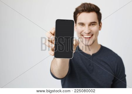 Positive young caucasian dark-haired male model with stubble in casual clothes demonstrating screen of smartphone and smiling cheerfully. Modern technologies. Advertising concept