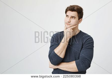 Dark-haired businessman with stubble keeps hand on chin, looks pensively aside, isolated against gray background. Confident handsome european guy with thoughtful expression of face.