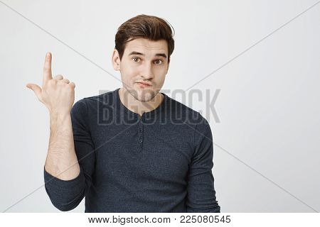 Portrait of annoyed and gloomy guy pointing up with index finger, showing gun while standing over gray background. Guy is irritated and tries to understand point of conversation.