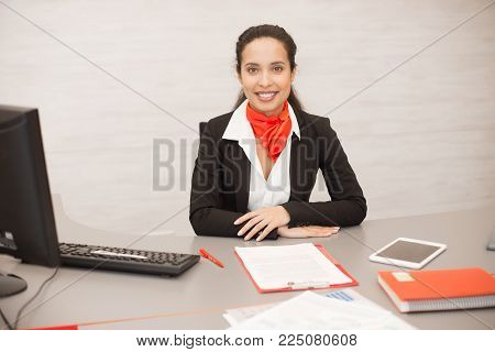 Portrait of cheerful mixed-race woman wearing black and red uniform sitting at desk in modern office smiling happily at camera, copy space
