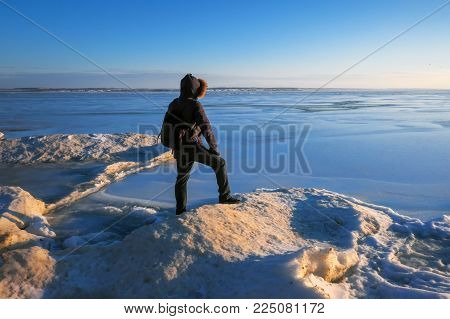 Man on the frozen river during sunset.